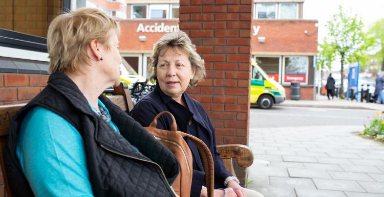 Two_Women_Sitting_Outside_Hosptial_Entrance