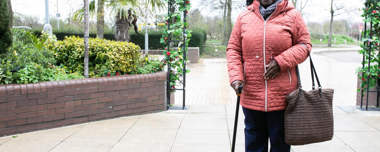 Woman stood in her coat leaning on her walking stick