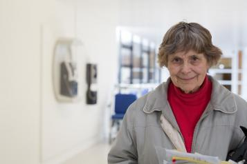 Elderly lady standing in a hospital corridor