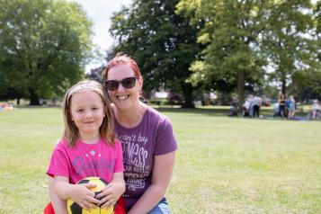 Mother with her arms round her daughter in the park