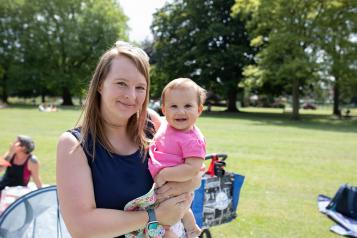 Woman in a sunny park with a young baby