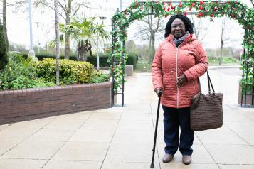 Woman stood outside in her coat leaning on a walking stick