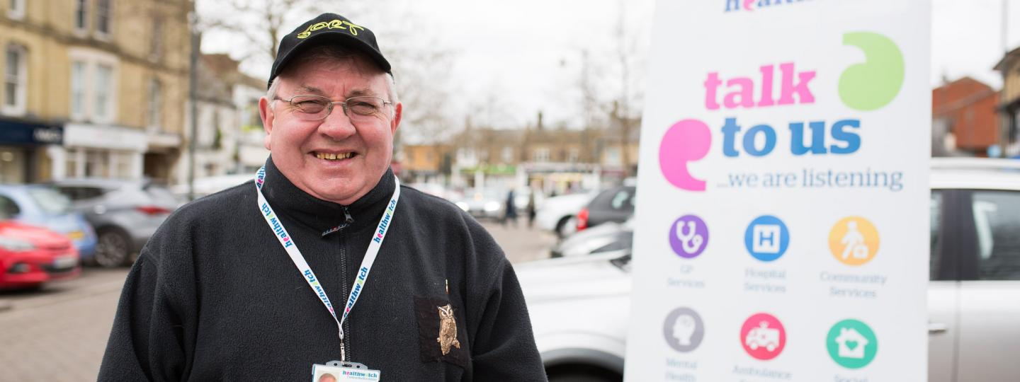 Man standing outside in front of a Healthwatch banner